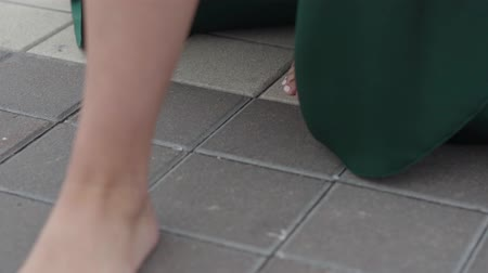 fashion outlet : Unrecognized girls bare feet in a long dress walking on city tiles.