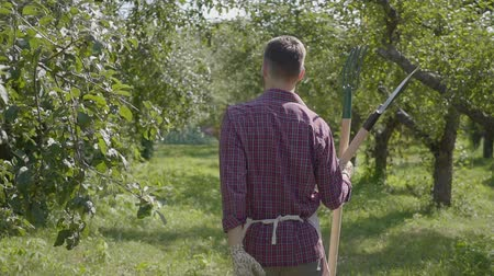 weeding : Professional bearded farmer walking through the garden with a shovel and pitchfork in hands. Concept of rural life, fruit-growing, gardening. Slow motion