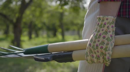 pikk : The farmer in garden gloves walking through the garden with a shovel and pitchfork in hands close-up. Concept of rural life, fruit-growing, gardening. Slow motion