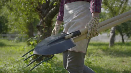desherbage : Unrecognized farmer in garden gloves walking through the garden with a shovel and pitchfork in hands close-up. Concept of rural life, fruit-growing, gardening. Slow motion Vidéos Libres De Droits