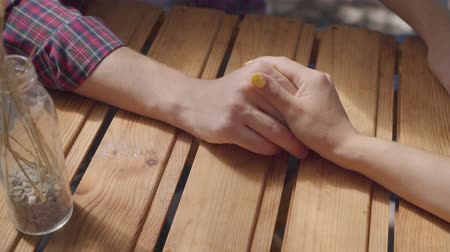 bağ : Close-up hands of unrecognized young guy and girl sitting outdoors at the table holding hands. Man and woman having date. Leisure at home. Tender relationship.