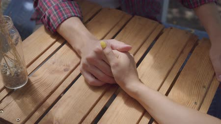 bağ : Close-up of male and female hands at the table outdoors. Man and woman having date. Leisure at home. Tender relationship.