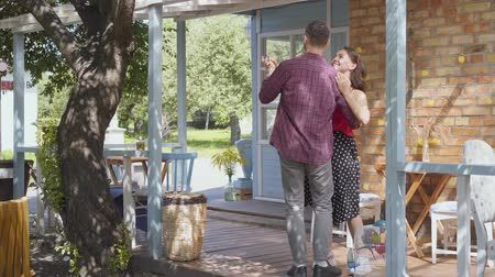 банкир : Young happy man and woman dancing on the porch of the old house smiling. Adorable couple having fun together. Leisure at home. Tender relationship.