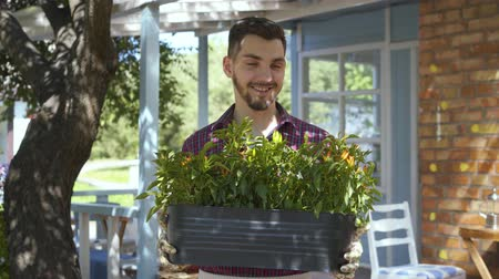 weeding : Portrait of young smiling bearded farmer holding a pot of flowers in hands looking at camera smiling standing in front of old house. Concept of rural life, growing, gardening. Real people series. Stock Footage