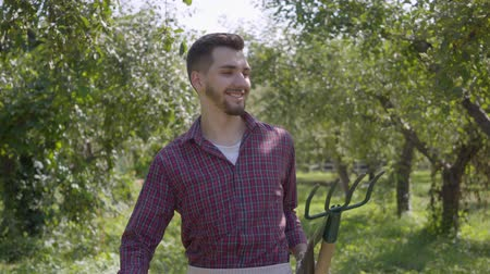 weeding : Confident young smiling bearded caucasian farmer walking through the garden with a spade and pitchfork checking fruit trees. Concept of rural life, fruit-growing, gardening.