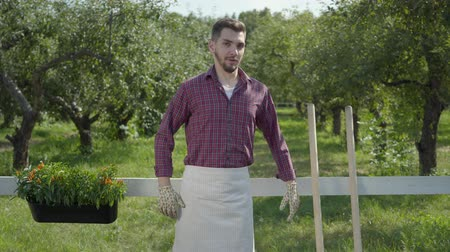 гитара : Funny young bearded farmer fooling around, imitating playing guitar using the pitchfork, then noticing camera and pretanding to be serious. Concept of rural life, fruit-growing, gardening. Real people