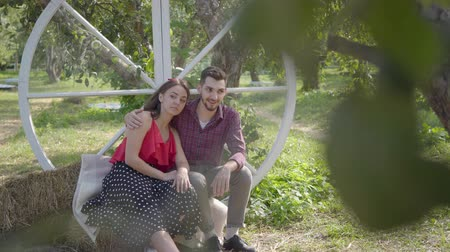 stories : Cute young woman and man sitting in the garden the guy hugging his girlfriend. Emotional woman telling her boyfriend interesting story. The relationship between husband and wife. Happy routine life