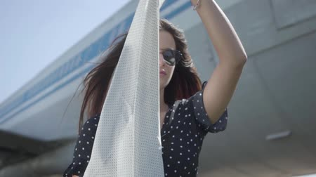 aircraft cabin : Portrait pretty brunette girl with the white shawl and sunglasses in front of the big plane and looking at camera. Summertime. Joy of travel. Concept of traveling, aircraft, weekend. Slow motion