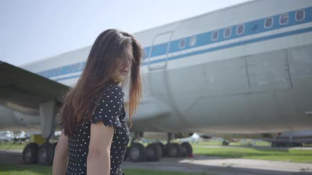 kanatlar : Young brunette girl with the white shawl in black dress turning away in front of the big plane. Summertime weekend. Joy of travel. Concept of traveling, aircraft, weekend. Slow motion Stok Video