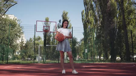 concentrar : Adorable teen brunette girl holding a basketball ball looking at the camera standing on the basketball court outdoors. Concept of sport, power, competition, active lifestyle. Sports and recreation.