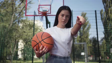 espectador : Attractive brunette woman with a basketball ball challenging viewer pointing her finger at the camera. Concept of sport, power, competition, active lifestyle. Sports and recreation.