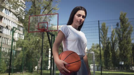 streetball : Portrait young brunette girl holding a basketball ball looking at the camera standing on the basketball court outdoors. Concept of sport, power, competition, active lifestyle. Sports and recreation. Stock Footage