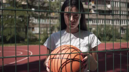 streetball : Portrait of brunette woman holding basketball ball looking at the camera standing behind the mesh fence at the basketball court. Concept of sport, competition, active lifestyle. Sports and recreation.