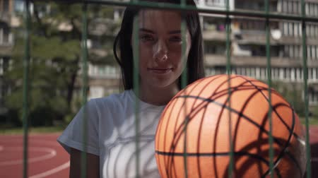 streetball : Cute brunette woman holding basketball ball looking at the camera standing behind the mesh fence at the basketball court. Concept of sport, competition, active lifestyle. Sports and recreation.