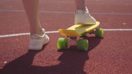 skateboard deck : Close-up of female legs in white sneakers next to a yellow skateboard on an outdoor basketball court. Concept of sport, competition, active lifestyle. Sports and recreation.