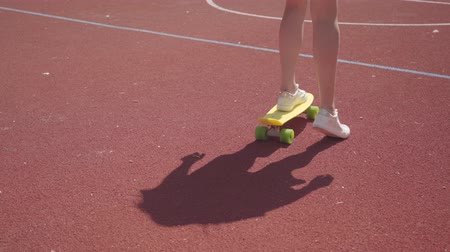 skateboard deck : Close-up of female legs in white sneakers girl riding yellow skateboard on an outdoor basketball court. Shadow follows the girl. Concept of sport, competition, active lifestyle. Sports and recreation.