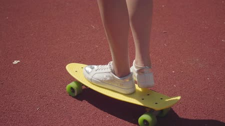 skateboard deck : Close-up female legs in white sneakers girl riding yellow skateboard on an outdoor basketball court. Concept of sport, competition, active lifestyle. Sports and recreation. Stock Footage