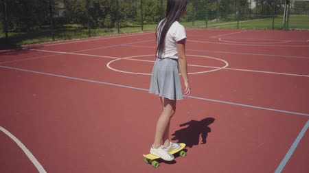 skateboard deck : Teen girl in sneakers, skirt and t-shirt riding yellow skateboard on an outdoor basketball court. Shadow follows the girl. Concept of sport, competition, active lifestyle. Sports and recreation. Stock Footage