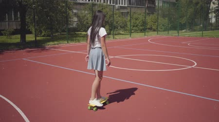 skateboard deck : Young girl in sneakers, skirt and t-shirt riding yellow skateboard on an outdoor basketball court. Shadow follows the girl. Concept of sport, competition, active lifestyle. Sports and recreation. Stock Footage