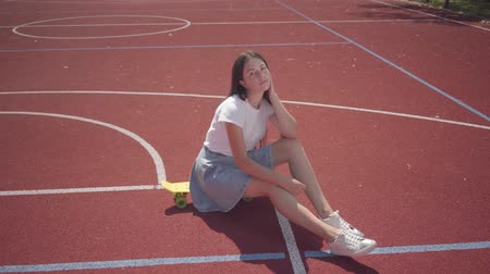 bruslař : Cute young brunette girl dressed in sneakers, a skirt and a T-shirt sits on a skateboard at outdoor basketball court in sunny summer weather. Concept of sport, active lifestyle. Sports and recreation. Dostupné videozáznamy