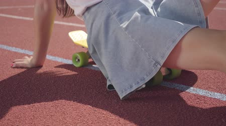 skateboard deck : Unrecognized girl sits on a skateboard at outdoor basketball court in sunny summer weather. Concept of sport, active lifestyle. Sports and recreation.