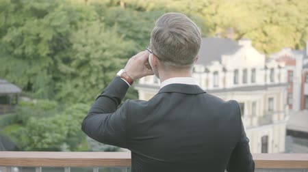 durulması : Back view of young ambitious successful businessman standing on the terrace drinking coffee. The office manager relaxing outdoors admiring nature. Break time, comfortable workplace, freelance. Stok Video