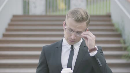 durulması : Portrait of handsome young well-dressed businessman in glasses standing in front of stairs with cup of coffee. The office manager waiting for the partner outdoors. Office lifestyle, business concept. Stok Video