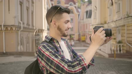 lő : Young newbie bearded photographer taking a photo in the street of an old city with beautiful architecture. Tourist takes picture of cityscape. Photography and tourism concept. Profession, creativity