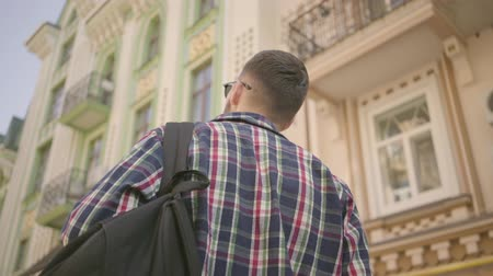 hayran olmak : Back view of young positive man with a backpack on the street in the old European city. Young tourist admiring beautiful cityscape alone. Travelling, tourism concept