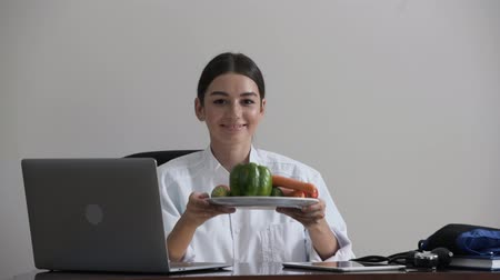 rekomendacja : Portrait of cute professional young female doctor offering vegetables as vitamins and healthy food sitting in the office. Concept of profession, medicine and healthcare. A good idea.