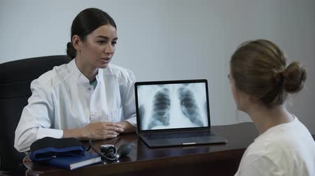 rekomendacja : Professional female doctor tells something to female patient and showing on screen of laptop with lung x-ray image. Women shake hands and the doctor closes the laptop. Concept of profession, medicine, healthcare. Wideo