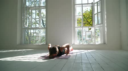 cobra : Slim caucasian woman standing on the mat in the large room practicing yoga. The girl slowly bending her body. Spiritual development