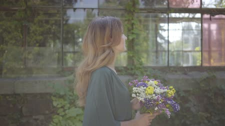 cheirando : Portrait of beautiful young woman walking with bouquet of wild flowers near building. Concept of summertime, rest day. Stock Footage