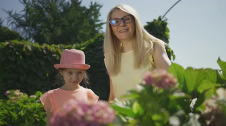 gündüz : Cute smiling mother in glasses shows her little daughter a blooming flower in the park. Happy family. Woman and girl together outdoors. Stok Video