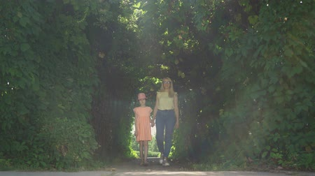 kids : Blond mother walking with daughter in the summer garden or park holding hands. Happy family. Connection with nature. Woman and girl together outdoors. Stock Footage