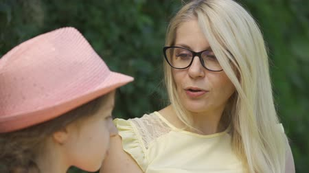 két : Portrait mature blond mother in glasses and her little daughter talking while sitting on the bench in the summer park. Happy loving family. Woman and girl together outdoors.