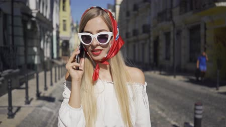 parisli : Portrait of cute young woman standing on the street talking by cellphone. Attractive fashionable girl enjoying sunny day in the old European city. Tourism concept Stok Video