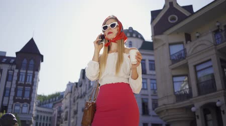 parisian : Fashionista woman with cup of coffee standing on the street in the sun and talking by cellphone. Attractive girl enjoying sunny day in the old European city. Tourism concept