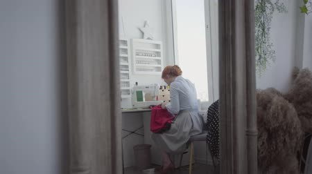 рукоделие : Beautiful red-haired woman sews clothes sitting at the table near the window in the light room. Seamstress works at home. Hobby. Sewing clothes