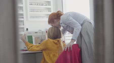 шов : Back view of little girl learning how to sew clothes sitting at the table near the window while her red-haired mother helping and teaching her. Seamstress and her daughter working together at home Стоковые видеозаписи