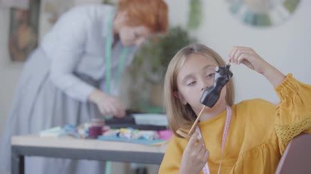 üzücü : Little sad daughter examines little dummy while her busy red-haired mother sews clothes in the background. Seamstress works at home. Lack of communication Stok Video