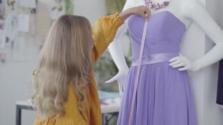 manequim : Beautiful little girl measuring elegant violet dress that hanging on a mannequin in the room. The child learning sewing clothes. Clothing design, profession Vídeos