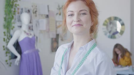 varrónő : Portrait of attractive red-haired seamstress looking at camera smiling while her little daughter drawing in the background. Happy family working together.