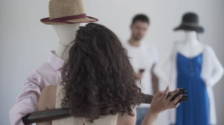 бюст : Back view of curly woman dancing with male mannequin in the hat while the man drinking wine in the background. Dreaming concept, imagination, loneliness