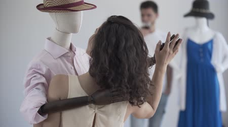 бюст : Back view of woman dancing with male mannequin in the hat while the man drinking wine in the background. Dreaming concept, imagination, loneliness