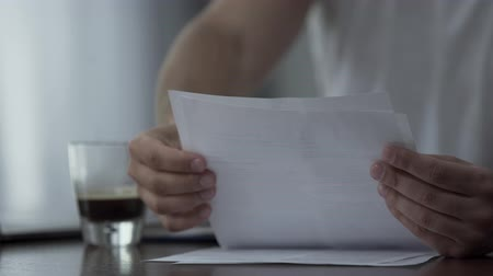 inacabado : Close-up of the man in white t-shirt working with papers and drinking coffee at home or in the office. The guy studying or working indoors. Freelance concept Stock Footage