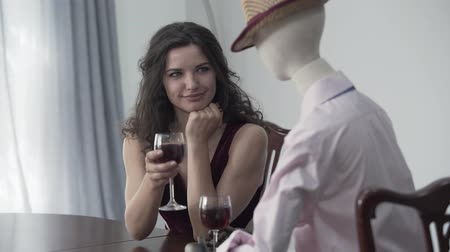 biust : Attractive curly woman sitting at the table drinking red wine with a male mannequin in the hat imitating date with the real man. Dreaming concept, imagination, loneliness