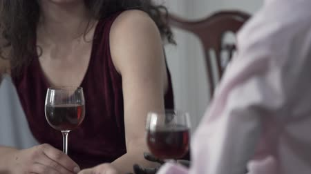 biust : Attractive curly woman sitting at the table drinking red wine with a male mannequin in the hat imitating date with the real man. Dreaming concept, imagination, loneliness. Camera moving down Wideo