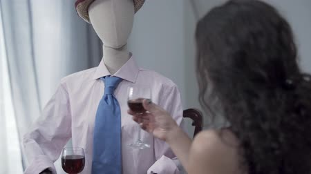 бюст : Cute curly woman sitting at the table drinking red wine with a male mannequin in the hat imitating date with the real man. Dreaming concept, imagination, loneliness