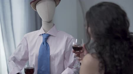 biust : Adorable curly woman sitting at the table drinking red wine with a male mannequin in the hat imitating date with the real man. Dreaming concept, imagination, loneliness